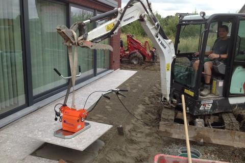 aanleg van terras in grote tegels met tegelzuiger